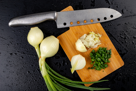 Fresh wet young onion on the kitchen table. Sliced chives on a kitchen board. Dark background.