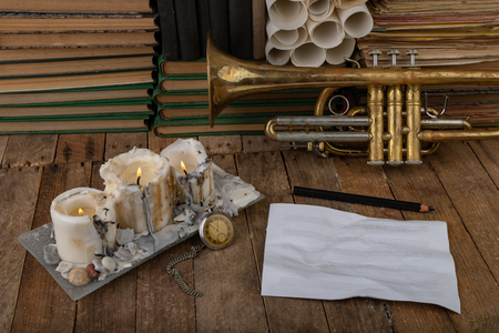 Old trumpet covered with patina on an old wooden table. Musical instrument and old books. Dark background.