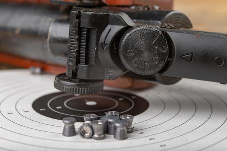 Broń pneumatyczna na drewnianym stole na strzelnicy. Akcesoria strzeleckie potrzebne do uprawiania sportów strzeleckich. Ciemne tło.