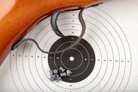 Un arma neumática sobre una mesa de madera en un campo de tiro. Accesorios de tiro necesarios para practicar deportes de tiro. Fondo oscuro.