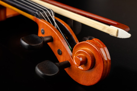 Beautiful new shiny violin on a dark table. Musical string instrument prepared for work. Dark background. Фото со стока
