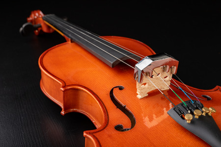 Beautiful new shiny violin on a dark table. Musical string instrument prepared for work. Dark background. Reklamní fotografie