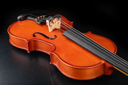 Beautiful new shiny violin on a dark table. Musical string instrument prepared for work. Dark background.