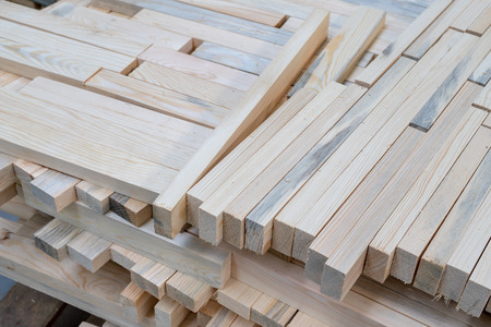 A pile of boards in a carpentry shop. Wood prepared for production in an industrial plant. Light background.