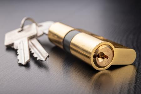 Una nueva cerradura de puerta sobre un fondo oscuro. Una patente y llaves para asegurar la puerta de entrada. Un fondo negro. Foto de archivo