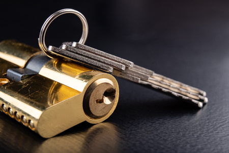 Una nueva cerradura de puerta sobre un fondo oscuro. Una patente y llaves para asegurar la puerta de entrada. Un fondo negro.