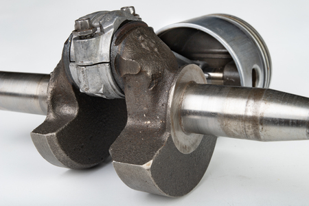 Piston and connecting rod of a small combustion engine. Components needed for mounting a high-power generator. light background.