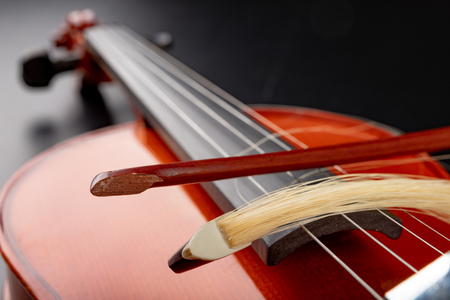 Broken bow to the violin. Damaged musical instrument. Dark background.
