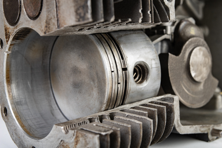 A four-stroke gasoline engine in section. The interior of a single-cylinder internal combustion engine. Dark background.