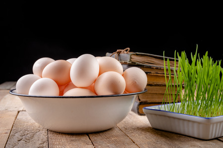 Eggs from hens on a wooden kitchen table. Fresh rye sprouts in a porcelain bowl. Dark background.