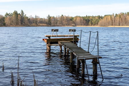 A wooden fishing bridge over a small lake. A place to catch fish. Season of the spring.
