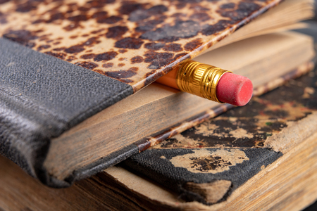Eraser bound on a pencil and an old book. Writing accessories and books on an old table. Dark background.