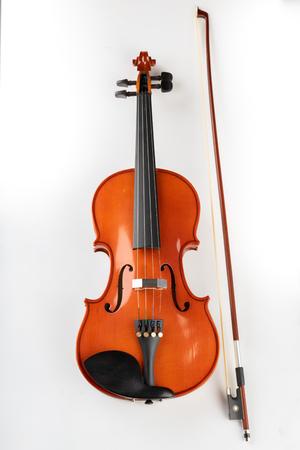 Violine und Bogen auf hellem Hintergrund. Ein neues Saitenmusikinstrument. weißer Hintergrund Standard-Bild