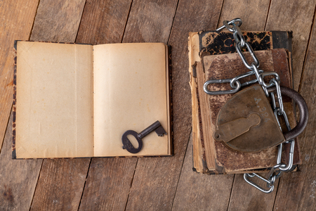 Old books bound by a new shiny chain with an old padlock. Forbidden old works artists on a wooden table. Dark background.