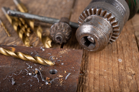 Drilling with a metal drill. Small locksmith work in the home workshop. Dark background.