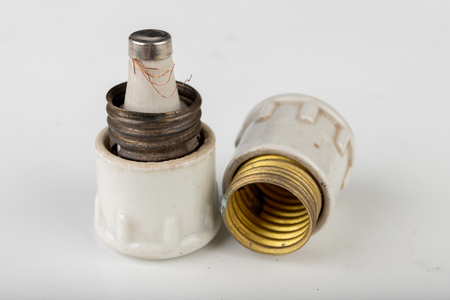 Old ceramic electric fuse. Blown and badly repaired security for energy, Bright background.