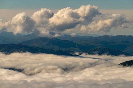 Mountains in Central Europe in the morning. The valley covered with a layer of clouds. Season of the spring.