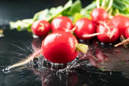 Ripe radish on a wet dark table. Water drops on vegetables in a home kitchen. Dark background. Reklamní fotografie
