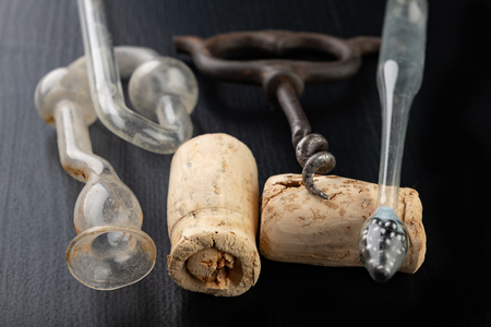 Fermentation tube and corkscrew on a black table. Accessories needed to prepare homemade wine. Dark background.