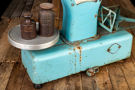 The old weight to weigh commodities from the communist era. Shop accessories on a stolen table. Dark background. Reklamní fotografie