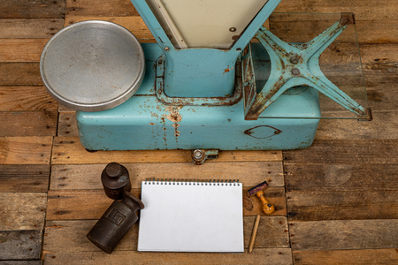 Equipment of the old store. Weight, notebook and goods on the shop table. Dark background.