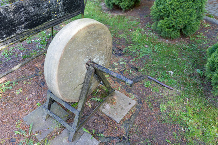 Old wheel for sharpening tools. Exhibit in the open-air museum in Central Europe. Season of the spring.