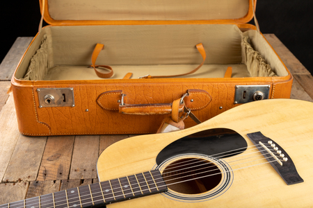 Classical guitar and suitcase on a dark wooden table. Stringed musical instrument on the go. Black background.
