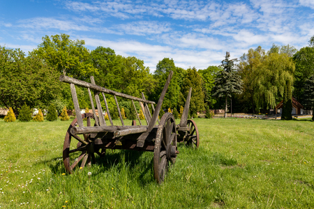 Old wooden wagon standing on a meadow in the countryside. Exhibit in skancenie in Central Europe. Season of the spring.