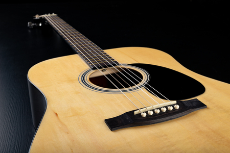 Classical guitar on a dark wooden table. Musical instrument stringed. Black background.