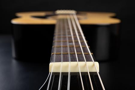 Klassieke gitaar op een donkere houten tafel. Muziekinstrument snaarinstrument. Zwarte achtergrond. Stockfoto