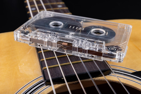 Acoustic guitar and cassette tape. Musical instrument and old music carrier. Dark background.