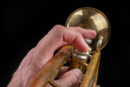 Old trumpet on a dark wooden table. Wind instrument in the old style. Black background. Stock Photo
