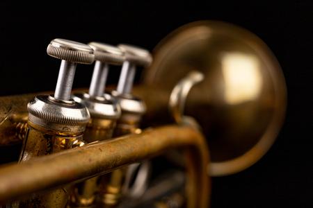 Ancienne trompette sur une table en bois sombre. Instrument à vent dans le style ancien. Fond noir.