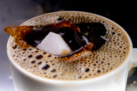 A sugar cube dropped into a cup with black coffee. Falling sugar into a warm drink. Dark background.