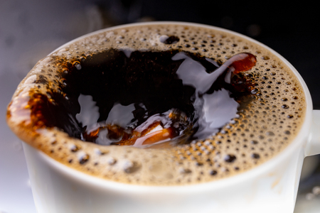 Spilled black coffee in a cup on a black table. Bad surface of the drink in the container. Dark background. 写真素材