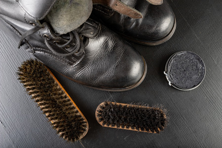 Shoe polish, brush and black military boots. Polishing and cleaning shoes on a black table. Dark background.