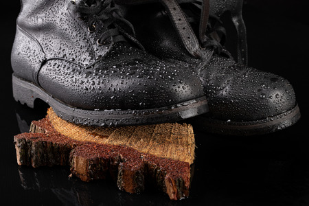 Black military boots and rain drops. Well-preserved old boots for soldiers. Dark background.