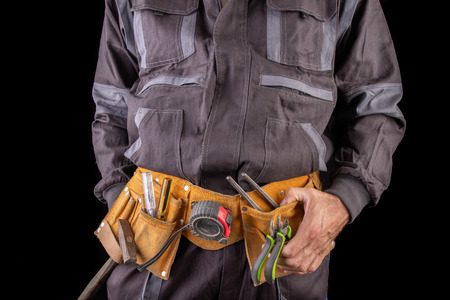 Workman in work clothes and tool belt. Production worker with a drill in his hand. Dark background. Reklamní fotografie