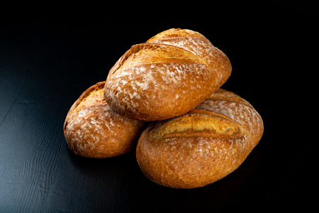 Freshly baked tasty bread on a dark table. Tasty baked goods straight from the bakery. Black background.