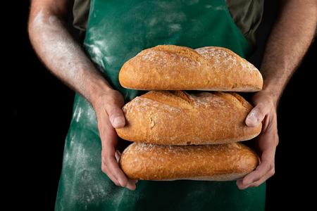 Freshly baked tasty bread in the bakers hands. Tasty baked goods straight from the bakery. Dark background. Stock Photo