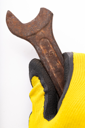 Old rusty damaged workshop key held in the palm of your hand. Accessories for a mechanic from an old workshop in a clean glove. Light background.