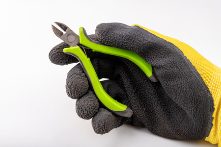 Pliers for cutting wire held in the palm of your hand. Cable cutter and hand in a clean work glove. Light background.
