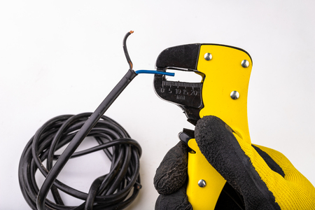 Device for removing insulation from electric cables. Accessories for the electrical installer. Light background. Imagens