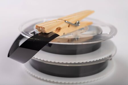 Tapes with a video recording are fastened with a washing clamp. Connecting and repairing old analog recordings. Light background.