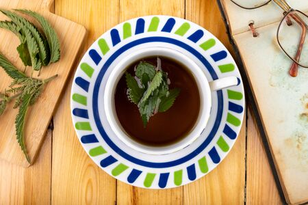 Tasty nettle tea in a cup. Freshly cut nettle and infected tea on a wooden table. Light background.