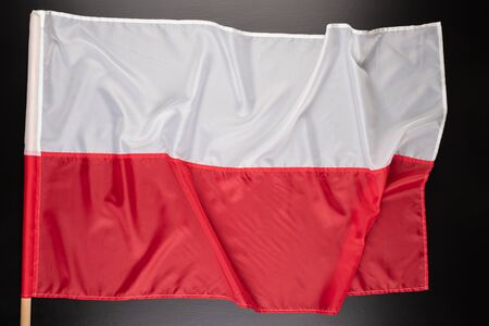 Polish flag on a dark table. A flag attached to a wooden spar. Dark background.