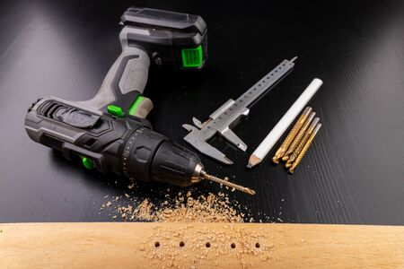 Drilling in a piece of dry planed wood. Holes made in the workshop with a screwdriver. Dark background. Stok Fotoğraf