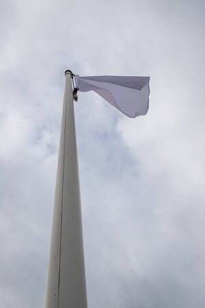 White flag on the mast near the beach. Flag on a background of cloudy sky. Season of the summer. Reklamní fotografie