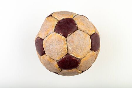 Old soccer ball to play on the leg on a white table. Leather and destroyed ball without air. Light background. Stock fotó