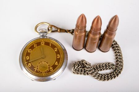 Old clock and ammunition on a white table. Explosive material and time measure. Light background.